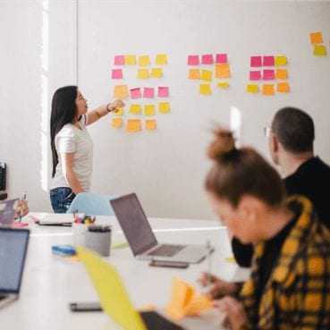 seo san diego office meeting with woman pointing at sticky notes on wall